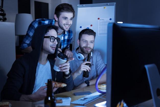 Na het werk. knappe positieve aardige mannen bier drinken en pizza eten tijdens het rusten na het werk