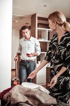 Na het winkelen. man kijkt toe hoe zijn vrouw al haar nieuwe kleren inpakt na het winkelen in de nieuwe stad