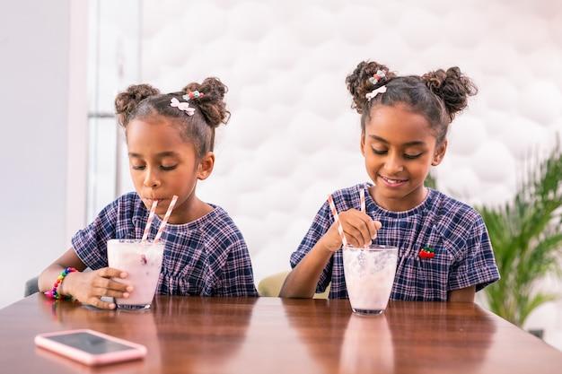 Na het winkelen. twee schattige kleine dochters die zich goed voelen terwijl ze hun milkshakes drinken na het winkelen met hun ouders