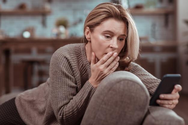 Na het zien van bericht. bezorgde vrouw met donkere ogen voelt zich emotioneel na het zien van bericht van echtgenoot