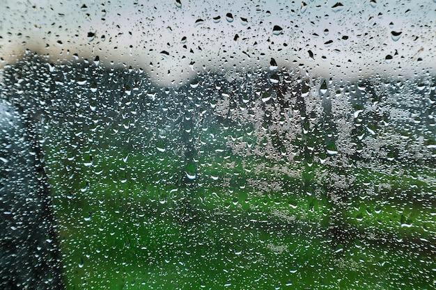 Na regen waterparels druilerig glazen raam van het resort.