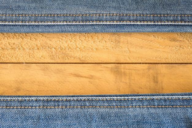 Naad van blauwe jeans op houten textuur