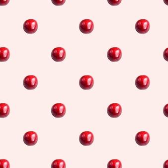 Naadloos patroon met kersen op een lichtrose achtergrond. minimale isometrische textuur van voedsel.