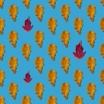 Naadloos patroon van droge gele en rode herfstbladeren op een blauwe achtergrond. textuurpatroon voor continu spelen voor design en creativiteit, natuurlijke achtergrond
