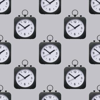 Naadloos patroon van klassieke horloges met handen op een grijze achtergrond.