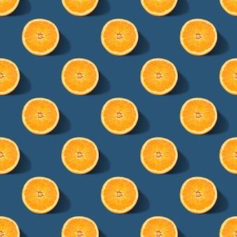 Naadloos patroon van sinaasappel dat op klassieke blauwe kleurenachtergrond wordt gesneden. minimaal, platliggend.