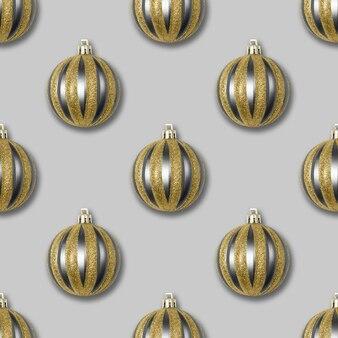 Naadloze patroon met gouden en zilveren kerstversiering op een grijze achtergrond.
