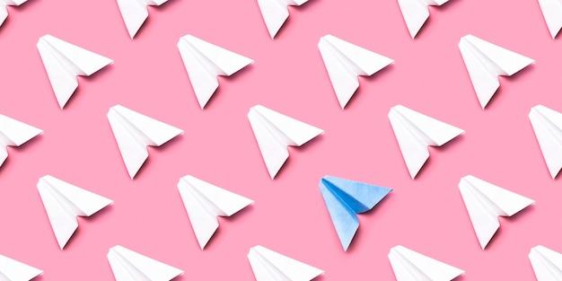 Naadloze patroon met papieren vliegtuigen op een roze achtergrond.