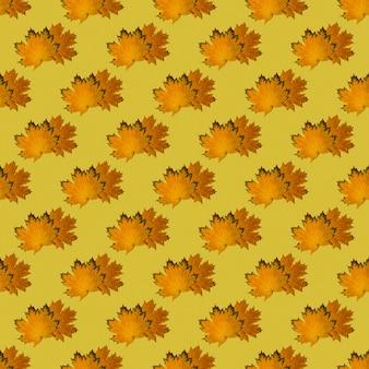 Naadloze patroon van droge herfst esdoorn bladeren op een felgele achtergrond. herfstprint op stof, inpakpapier. kan worden gebruikt als een natuurlijke achtergrond