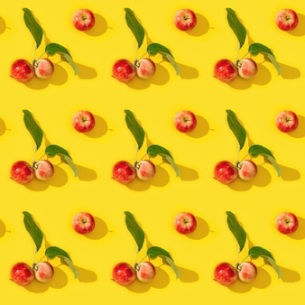 Naadloze patroon van rijpe kleine rode appels en groene bladeren op geel