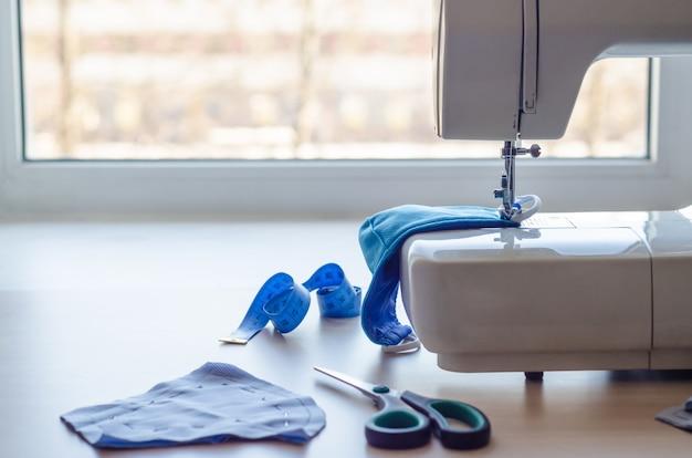 Naai het gezichtsmasker thuis. beschermende uitrusting bij epidemie van coronavirus.