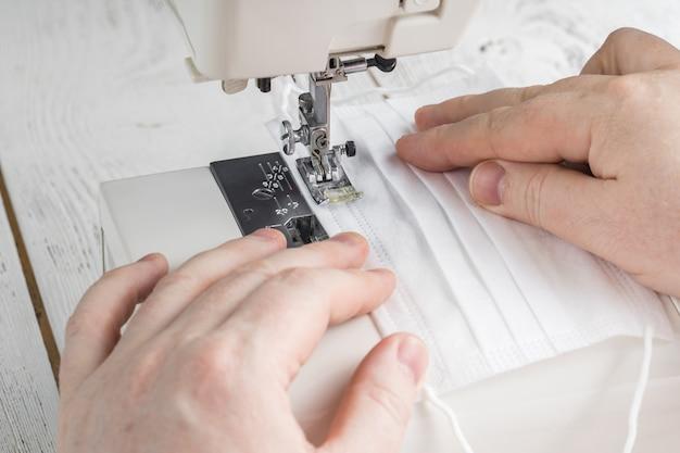 Naai het textielgezichtsmasker tijdens coronavirus pandemie met een naaimachine. hoe maak je een zelfgemaakt medisch masker van steriel gaas. bescherming tegen virussen en besmette lucht. selectieve aandacht
