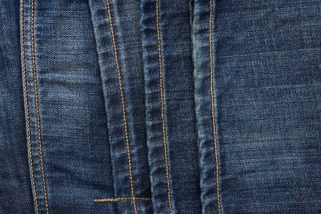 Naai op een blauwe spijkerbroek met bruine draad