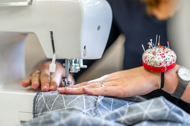 Naai thuis en in de studio gekleed op een naaimachine.