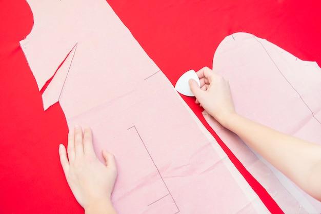 Naaiatelier. een naaister omcirkelt een kledingstuk op een stof. kleding naaien. rode doek