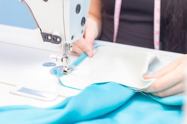 Naaiatelier. naaister naaien op een naaimachine close-up. een set items voor handwerk: draden, naalden, pinnen, schaar, meetlint, enz.