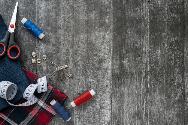 Naaibenodigdheden, jeans en geruite stof op een donkere houten achtergrond.