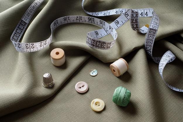 Naaibenodigdheden liggen op gedrapeerde stof, close-up. naaien achtergrond. klosjes draad, een centimeter, een schaar, een vingerhoed, op een grijze gedrapeerde doek. atelierconcept. mode ontwerper. naaien samenstelling.