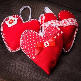 Naaide handgemaakte rode harten op houten achtergrond
