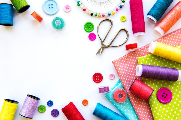 Naaien accessoires en stof op een wit oppervlak. naaigaren, naalden, spelden, stof, knopen en naai-centimeter. bovenaanzicht, plat gelegd.