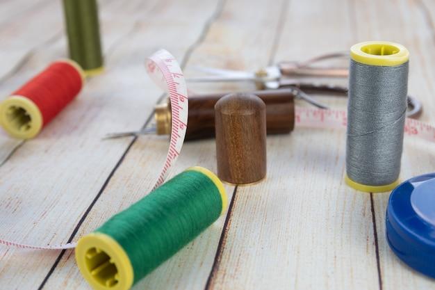 Naaien achtergrond. accessoires voor handwerk op houten achtergrond. spoelen van draad, schaar, meetlint, naaibenodigdheden. instellen voor handwerk bovenaanzicht