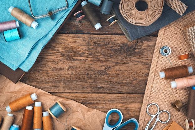 Naaien achtergrond met een set naai-accessoires op een houten achtergrond.