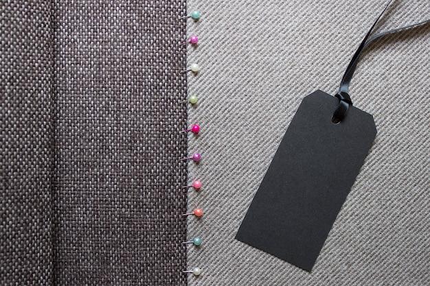Naaien achtergrond met geweven stof en zwart papieren label op satijnen touw