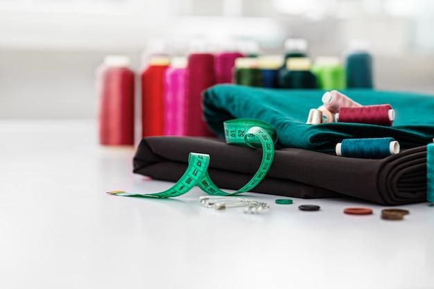Naaien achtergrond. reeks hulpmiddelen op maat op witte achtergrond. naai-accessoires: schaar, draden, naalden, spelden, stof, knopen, meetlint. werkplek van naaister. bovenaanzicht met kopie ruimte.