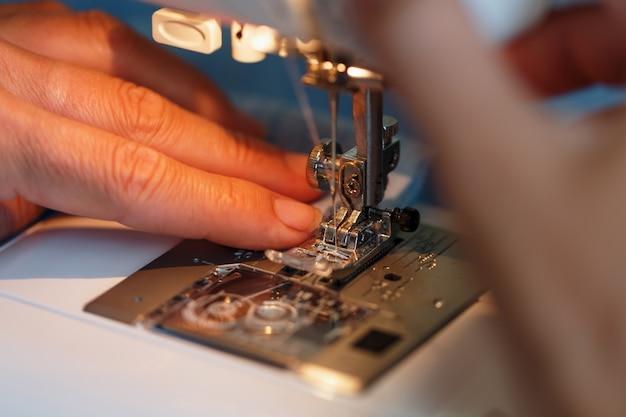 Naaien kleding op een naaimachine close-up.
