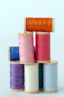 Naaien. kleurrijke draden op een witte achtergrond