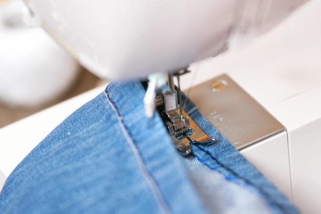 Naaiende denimjeans met naaimachine. repareer jeans per naaimachine.