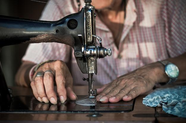 Naaiende proces door de uitstekende naaimachine op het onduidelijke beeldachtergrond van de oude mensenontwerper
