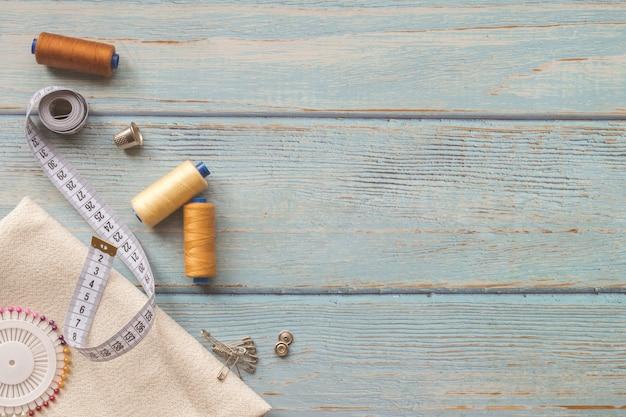Naaiende toebehoren en stof op een blauwe achtergrond. stof, naaigaren, naald, knopen en naai-centimeter. bovenaanzicht, flatlay, copyspace