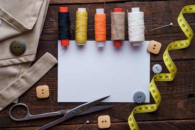 Naaigarnituur en diverse naai-accessoires voor het naaien voor naaister op donkere houten achtergrond bovenaanzicht. kopieer ruimte