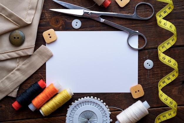 Naaigarnituur en verschillende naaibenodigdheden voor handwerk voor naaister op donkere houten achtergrond