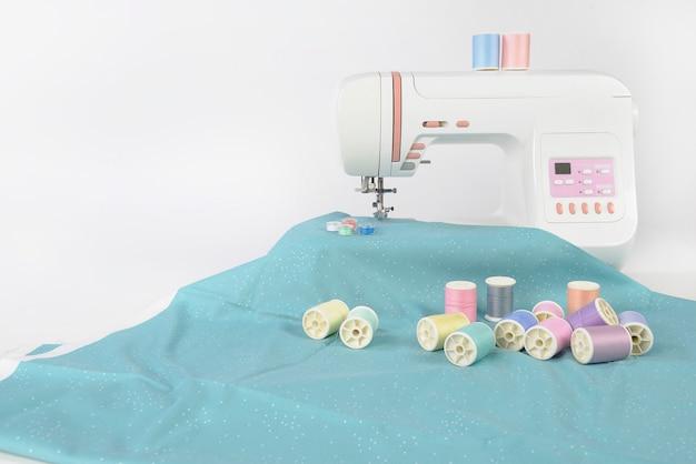 Naaimachine en kleurrijke draadrollen, schaar, stof en toebehoren om te naaien.