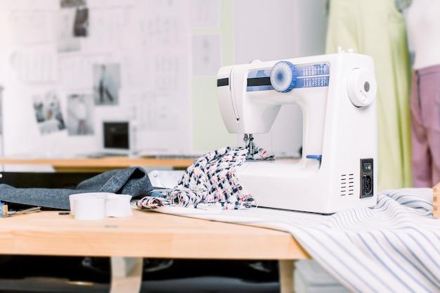 Naaimachine met stof op tafel in kleermaker workshop. professionele naaimachine op de achtergrond van atelier studio. naaimachine, draadrollen, stof, schaar. naaien bedrijfsconcept.