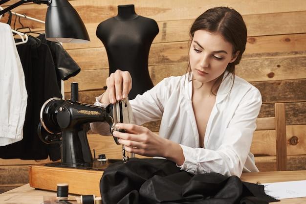 Naaimachine moet correct worden behandeld. geconcentreerde vrouwelijke ontwerper naait kleding in de werkplaats, steekt de draad in de aansluiting en probeert het kledingstuk op tijd af te werken om het aan de klant te geven. outfit ziet er geweldig uit
