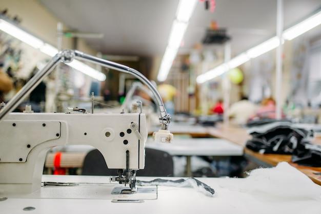Naaimachine op kledingstof, niemand. kleermakerij, uitrusting op kledingfabriek, professionele kleermakerij