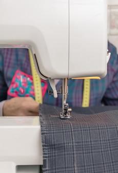 Naaimachinenaald en naaister op achtergrondgeluid