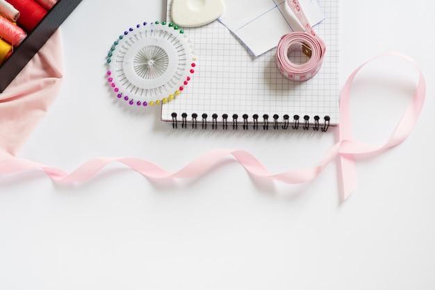 Naaimaterialen - een doos met draden van felle kleuren, een roze lint, katoen, meetlint op een witte achtergrond. frame, ruimte voor tekst