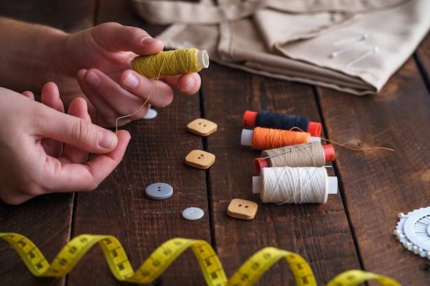 Naaiset voor handwerk op houten oppervlak. spoel van draad in de handen van een naaister