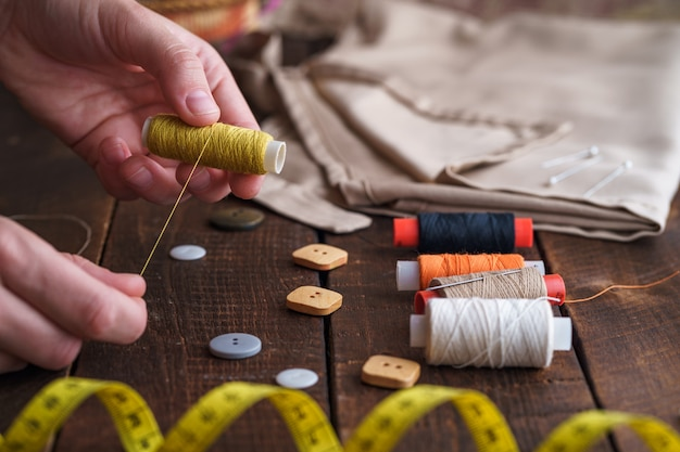 Naaiset voor het maken op houten oppervlak. spoel van draad in de handen van een naaister