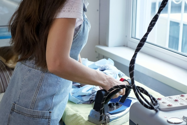Naaister die details van kleding strijkt in het naaiatelier van het op maat maken van zaken.