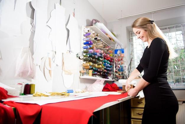 Naaister die jurkstof op schetslijn snijdt met naaimachine. bedrijfseigenaar winkel en ondernemer concept.