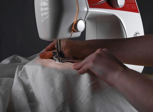 Naaister hand bij naaimachine tijdens werkproces met katoen