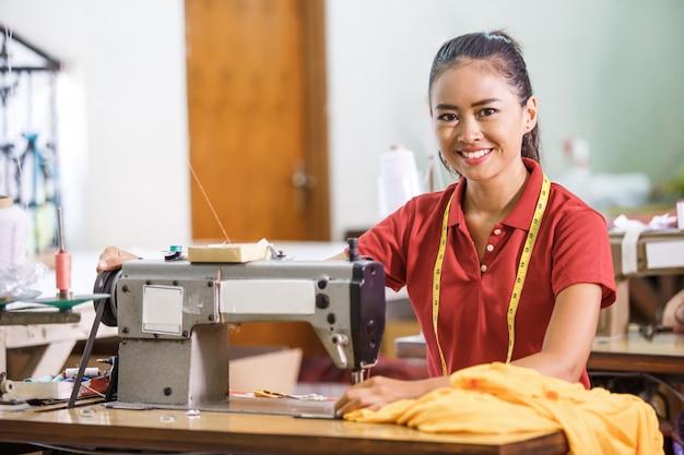 Naaister in textielfabriek die terwijl het naaien glimlacht