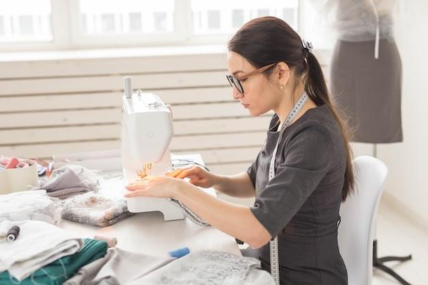 Naaister, kleermaker en creatief concept - portret van modeontwerper met naaimachine over witte muur