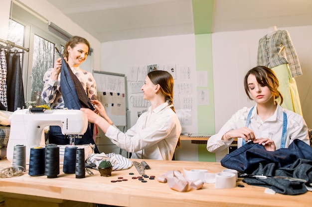 Naaister, kleermaker, mode en showroomconcept - portret van drie jonge getalenteerde vrouwelijke naaisters die nieuwe modieuze stijlen van broeken en kleding creëren.
