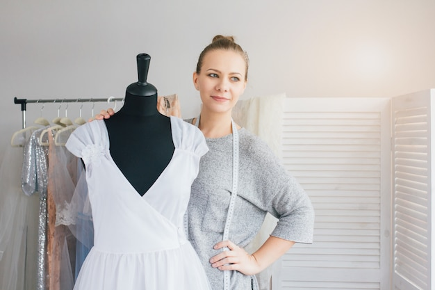 Naaister maakt een jurk passend op de mannequin